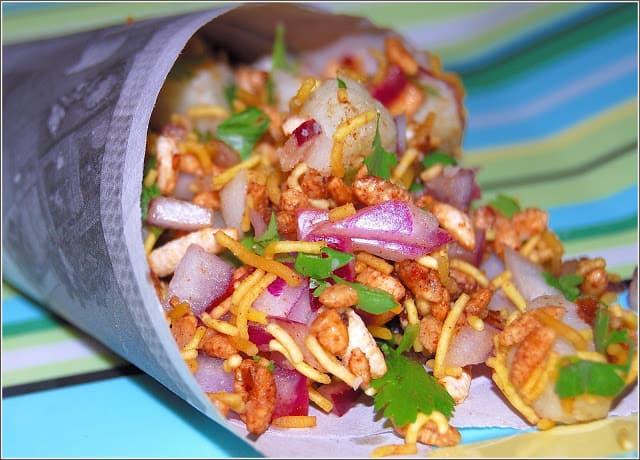 Photo of bhel wrapped in a newspaper cone exactly as it would if you bought it on a Bombay beach.