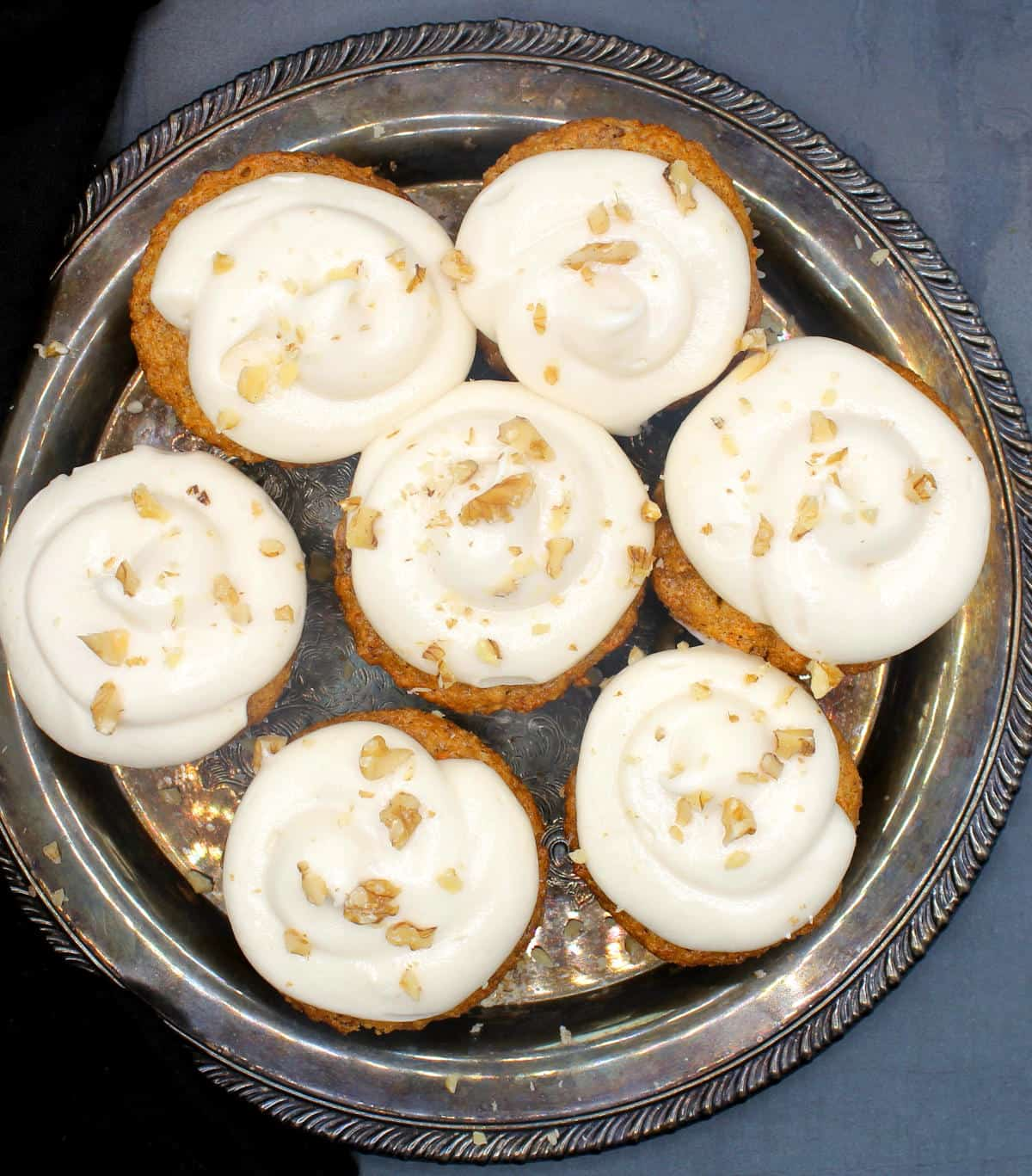 Overhead shot of vegan carrot cupcakes with vegan cream cheese frosting on a silver plate)