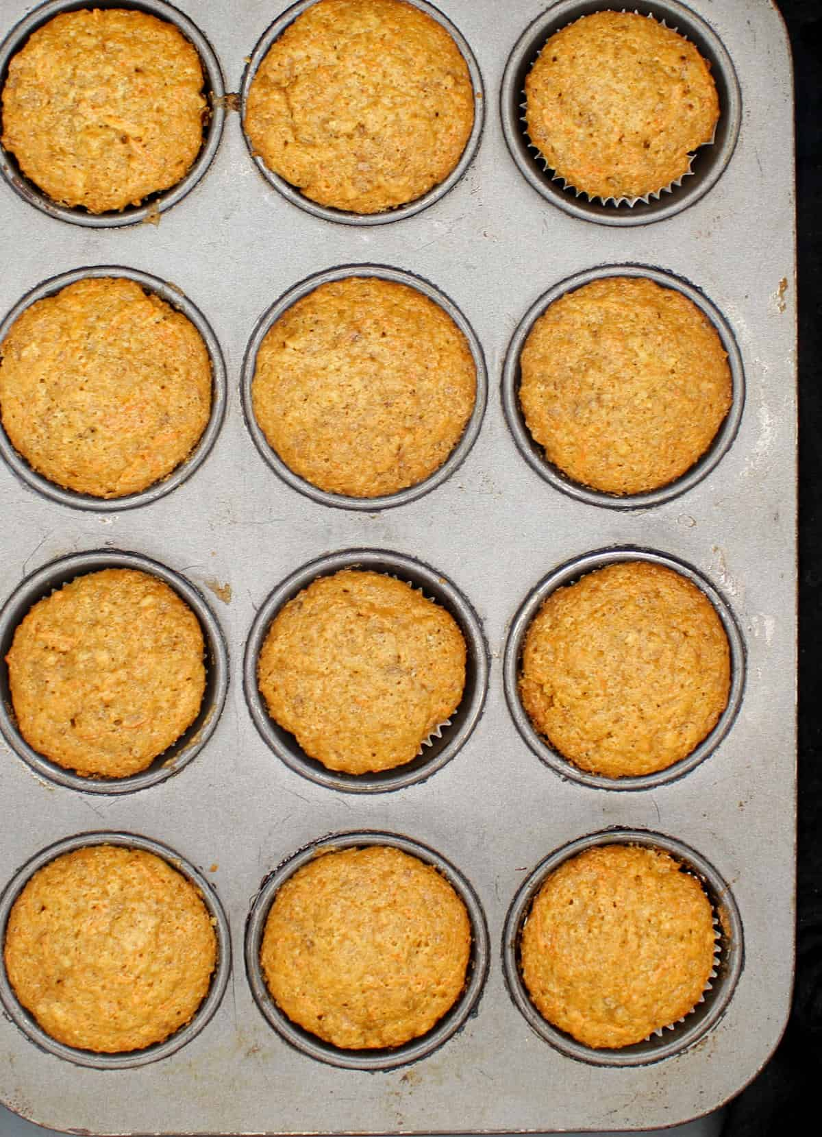 Vegan carrot cupcakes, freshly baked, in a muffin pan.