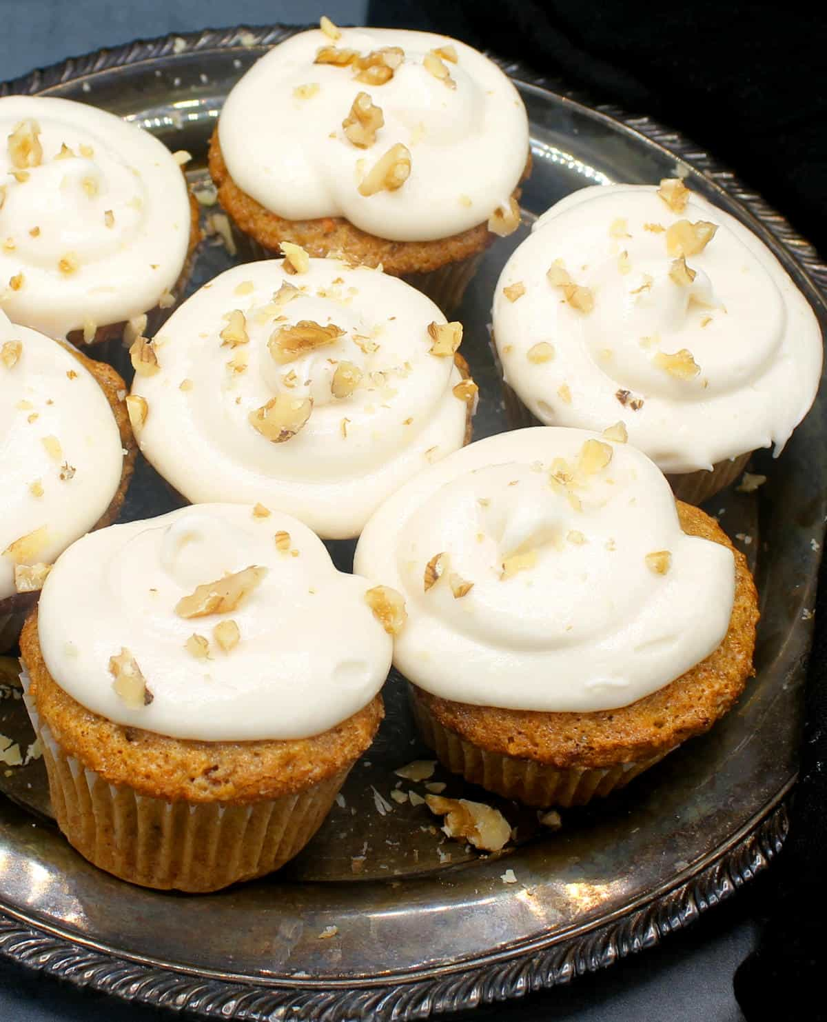 Vegan carrot cupcakes with cream cheese frosting on a silver plate with walnuts scattered on top.
