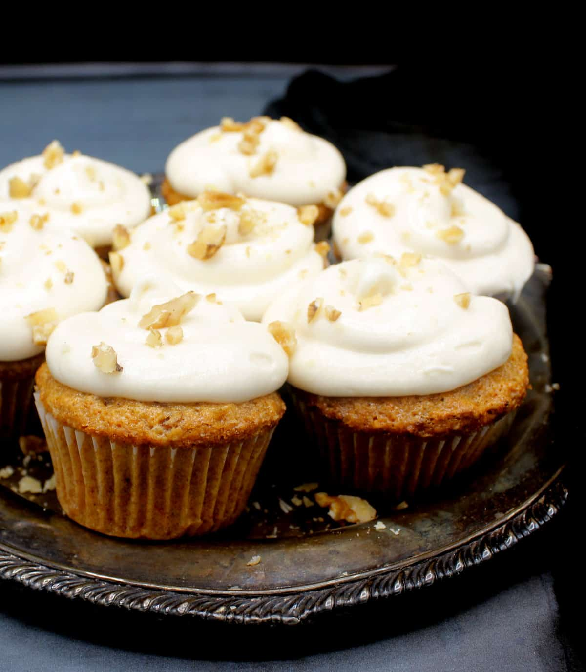 Close front shot of vegan carrot cupcakes with cream cheese frosting and walnuts scattered on top in a silver plate.