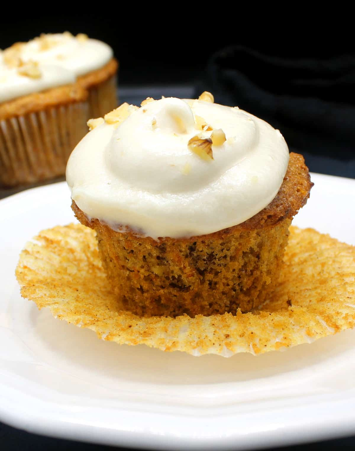 A single vegan carrot cupcake with cream cheese frosting and walnuts on top in a white plate with more cupcakes in the background.