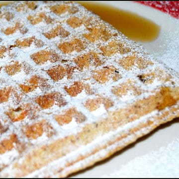 Vegan waffle with wheat germ and flaxmeal on a white plate with maple syrup
