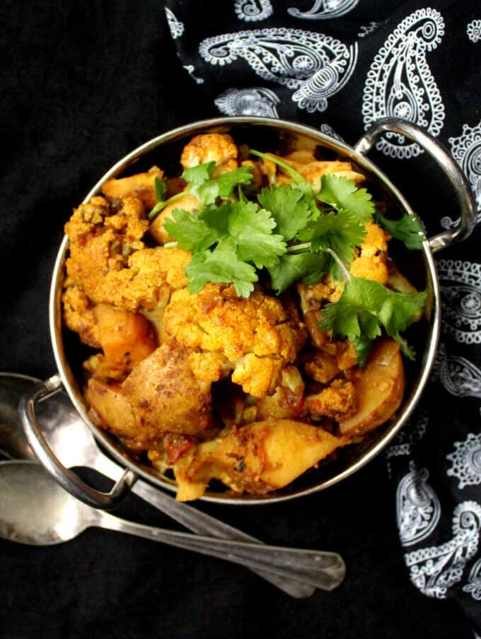 Aloo Gobi, or cauliflower and potatoes sauteed with Indian spices, is a tasty side that goes perfectly with roti, paratha, or dal and rice. #Indian #vegan #dinner #side #vegetarian #recipe HolyCowVegan.net