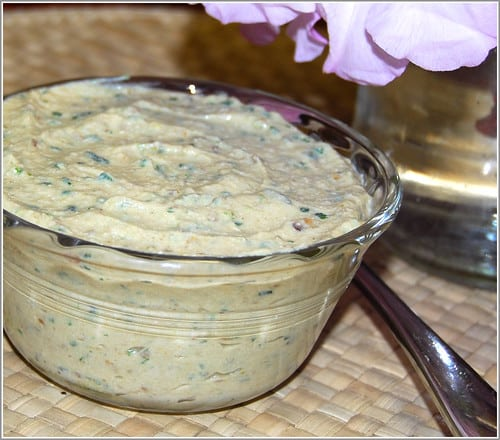 Creamy eggplant and tofu dip in a glass bowl with a flower and a spoon in background