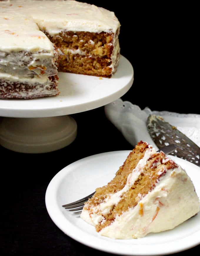 Photo of Vegan Orange Cake with Orange Marmalade Buttercream Frosting on a cake stand with a slice in front on a white plate.