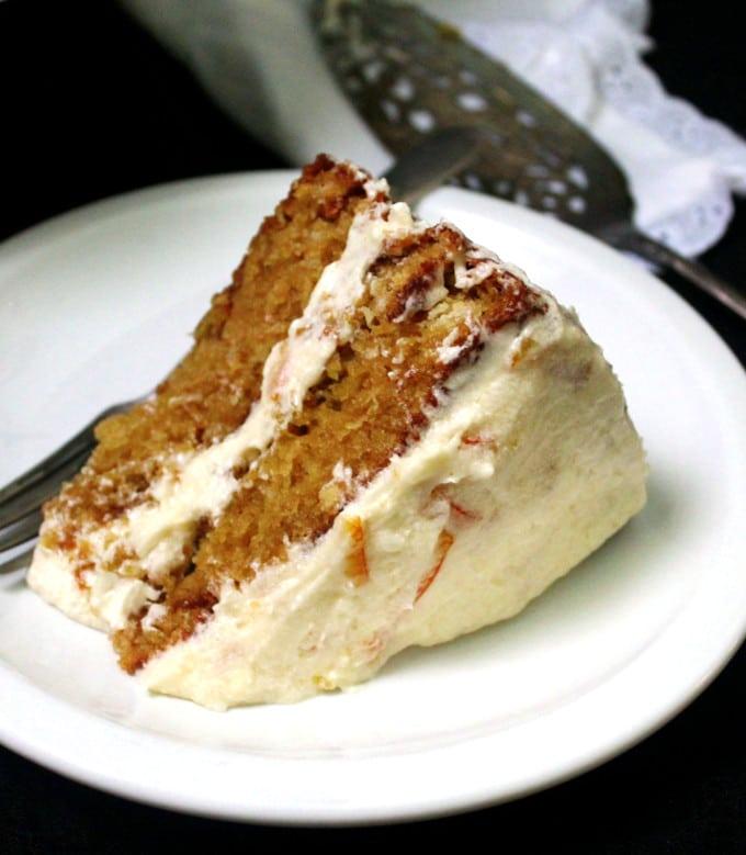Closeup of a slice of vegan orange cake with orange marmalade buttercream frosting.