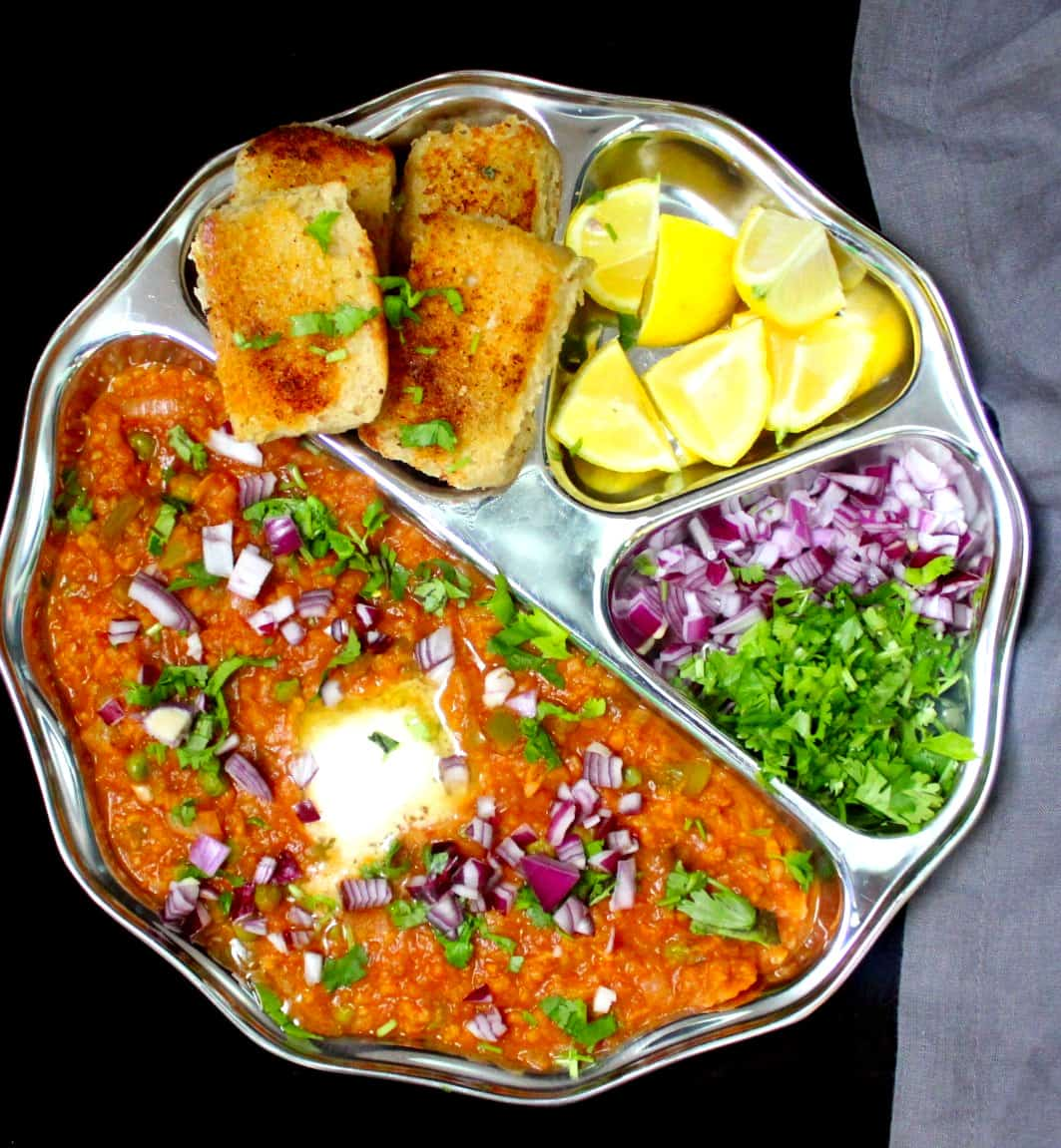 An overhead shot of a plate of pav bhaji with the mashed veggies, pav, lemons onions and cilantro