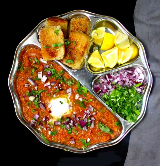 A steel plate with compartments with pav bhaji, toasted, buttered pav, lemons, cilantro and onions.