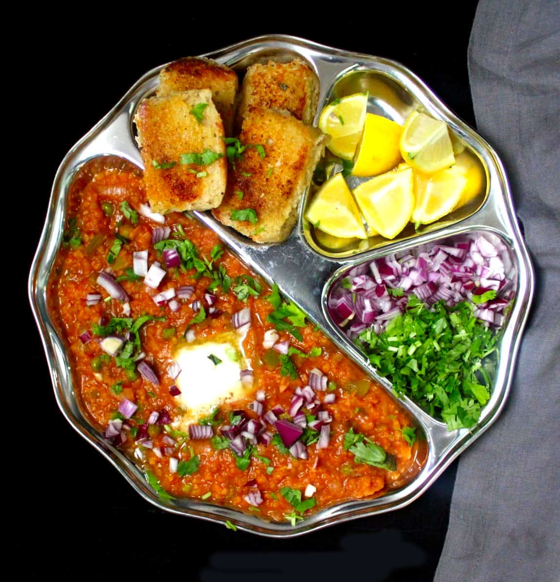 Photo of pav bhaji served in a steel plate with compartments, with toasted, buttered pav, lemons, cilantro and onions.