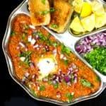 An overhead shot of a plate of pav bhaji with the mashed veggies, pav, lemons onions and cilantro
