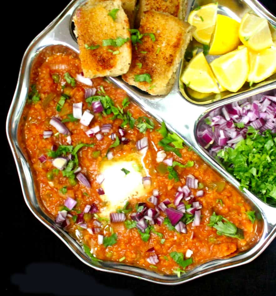 An overhead close up of a plate of pav bhaji with orange-red bhaji, toasted pav, lemons, onions and cilantro