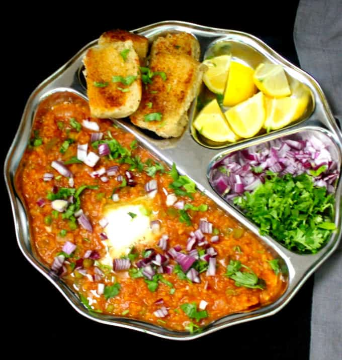 A front shot of pav bhaji in a steel plate with all the trimmings--onions, butter, lemon and cilantro on a black table.