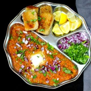 A steel plate with pav bhaji, with butter, lemons, onions and cilantro