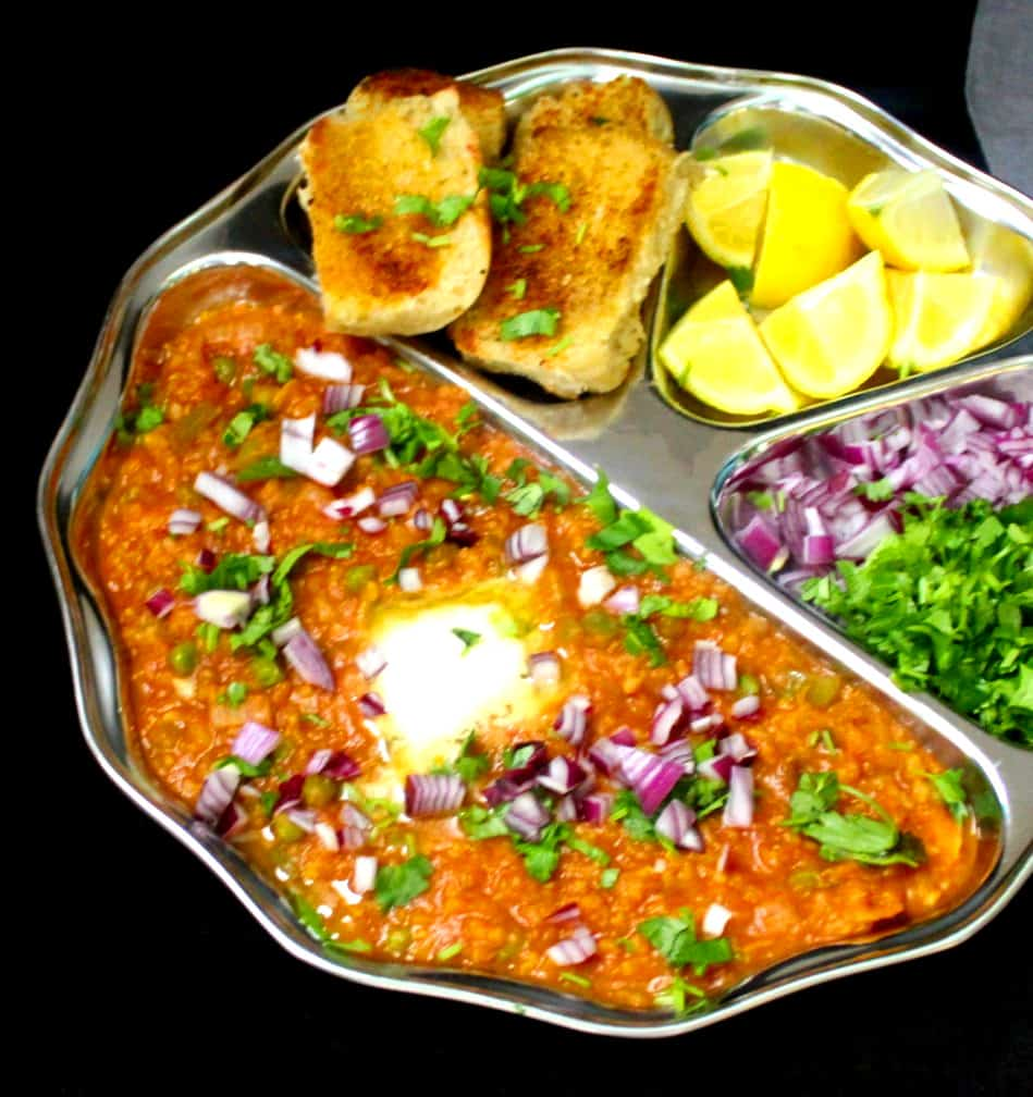 A front partial shot showing a closeup of the bhaji in pav bhaji with lemons, pav bread rolls, onions and cilantro