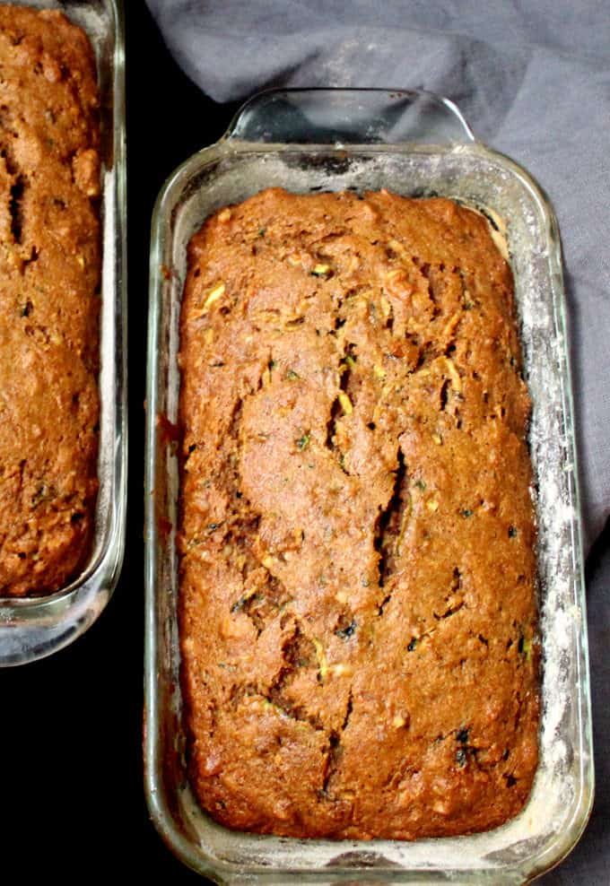 Top view of two glass loaf pans with golden, fresh-baked loaves of zucchini bread, with a gray napkin in the background.