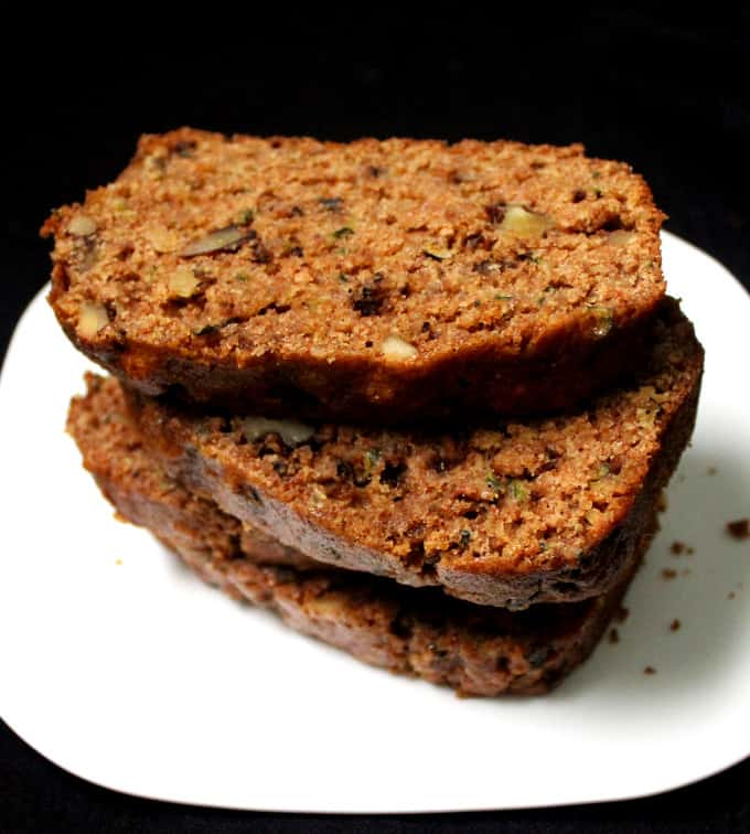 Vegan Zucchini Bread slices in a white plate with healthy walnuts, whole wheat flour and cinnamon