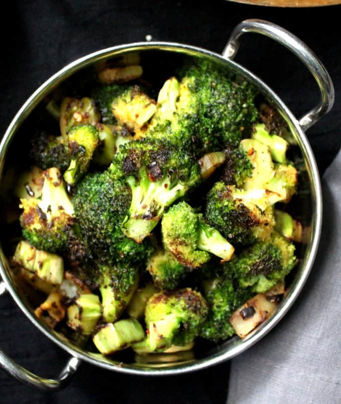 A close up shot of garlicky broccoli florets with red pepper flakes