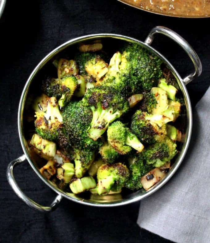 Green broccoli florets and stems stir-fried and served in a steel bowl