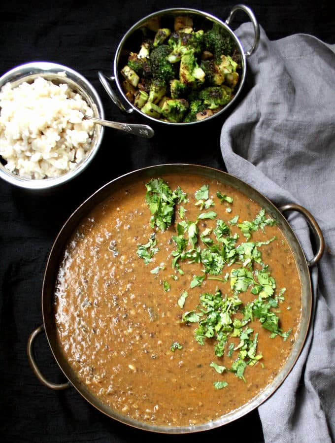 Top shot of spicy urad dal with brown rice and broccoli sabzi and a gray napkin