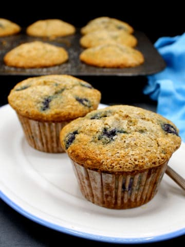 Vegan Blueberry Muffins in a white and blue plate with a muffin pan in the background