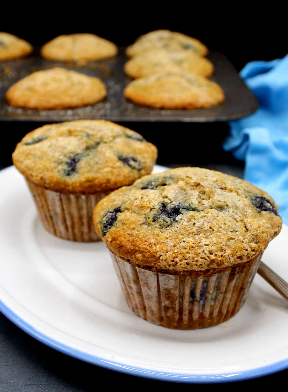 Front shot of two golden vegan blueberry muffins with the muffin pan in background.