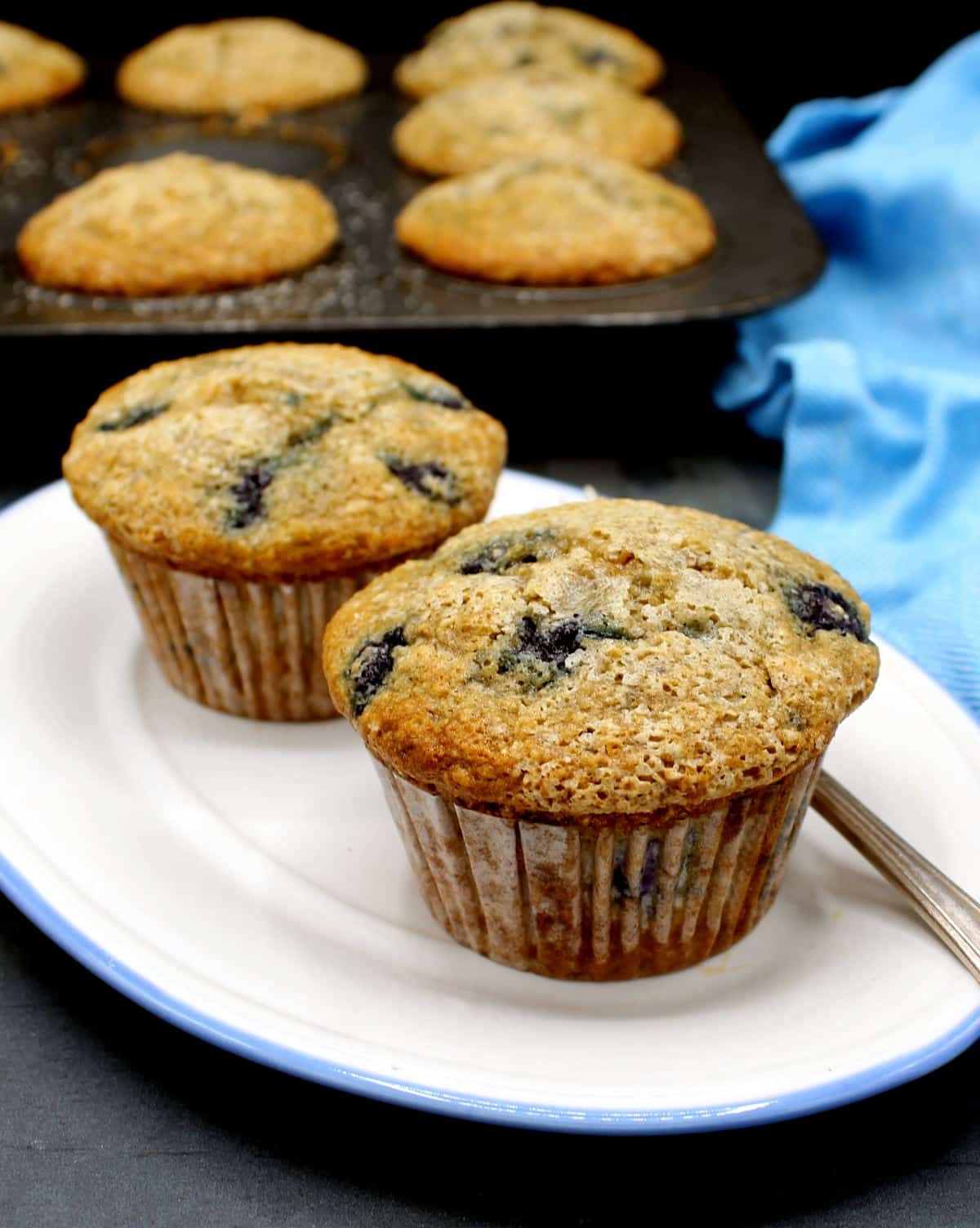 Two vegan blueberry muffins on a white and blue plate with the muffin tin with more muffins in background with a blue napkin.