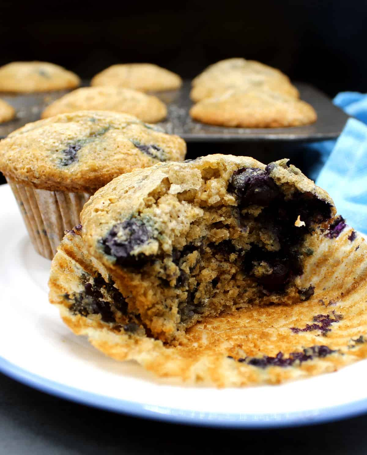 Cross section of a blueberry muffin that shows a moist, light, airy, wholegrain crumb packed with pockets of juicy blueberries.