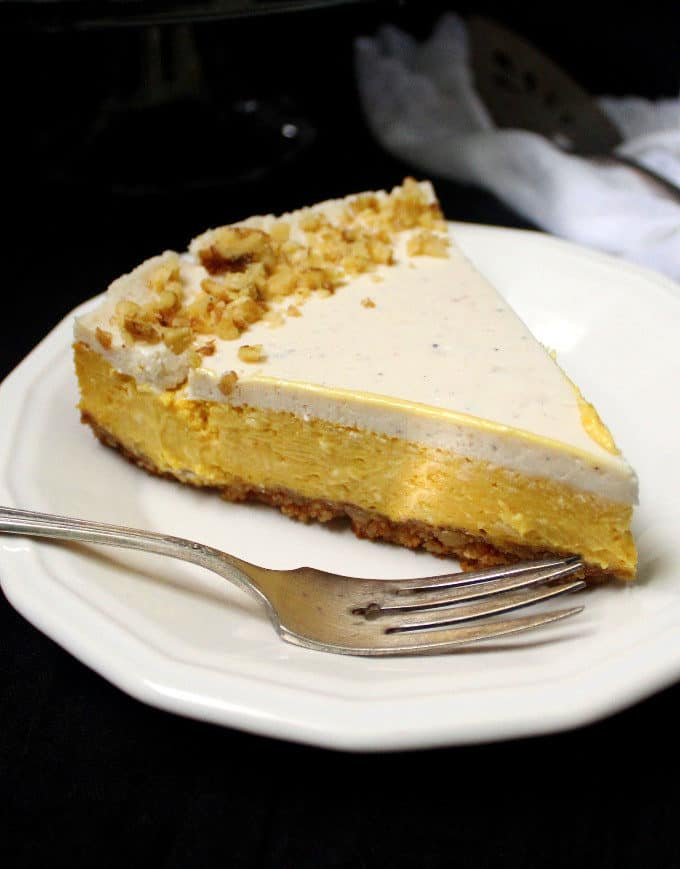 Close-up shot of a slice of vegan mango cheesecake with a graham cracker crust, sour cream topping and walnuts scattered on top.