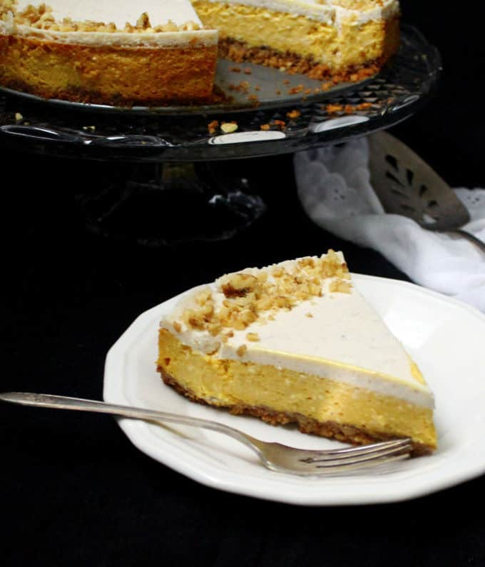 A slice of mango cheesecake with a graham-cracker-walnut crust on a white plate with a fork on the side and in the background is the full cake on a crystal cake stand with a silver serving spoon and a white lace napkin on the side.