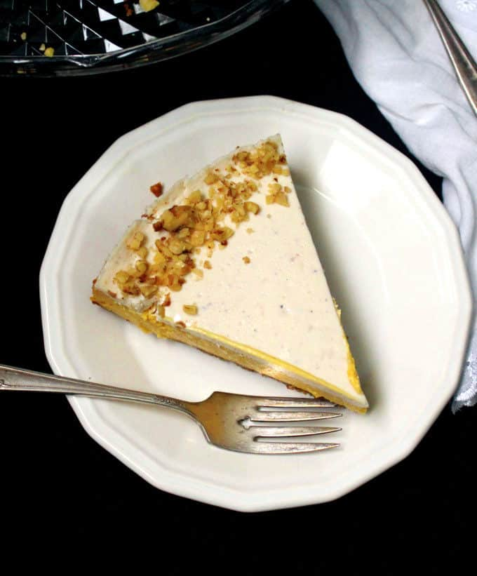 Top shot of a vegan mango cheesecake slice with walnuts scattered on top and sitting on a white plate with a decorative fork next to it, set against a black background.
