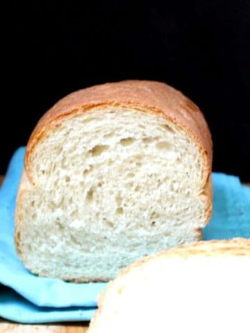 A close up shot of a cross-section of a perfectly baked sandwich bread on a blue napkin