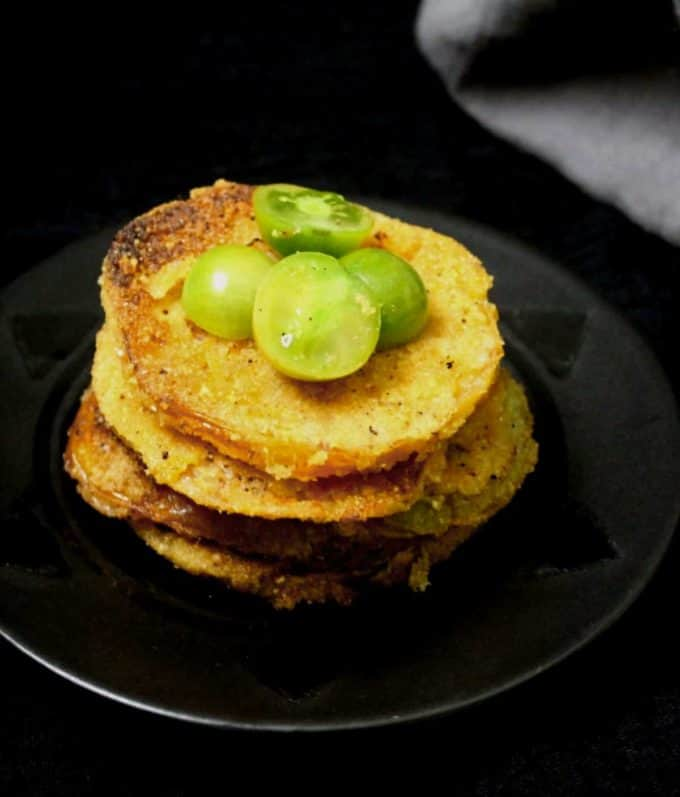 A black plate with slices of vegan fried green tomatoes stacked over it and a gray napkin in the background