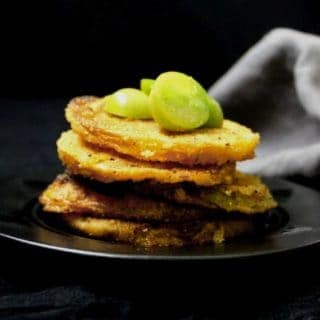A stack of golden, crispy fried green tomatoes with small green cherry tomatoes on top and a gray napkin in the background