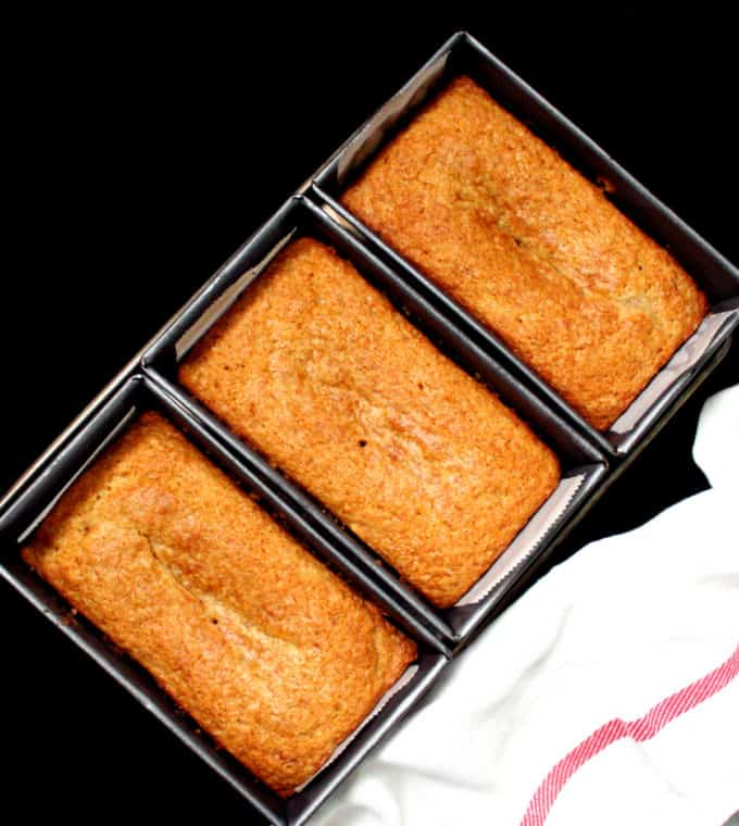 Three loaves of vegan mawa cake, and Irani restaurant delicacy from Bombay, in mini loaf pans with a white and red napkin.