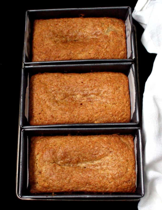 Three loaves of vegan mawa cake in min loaf pans with a white napkin