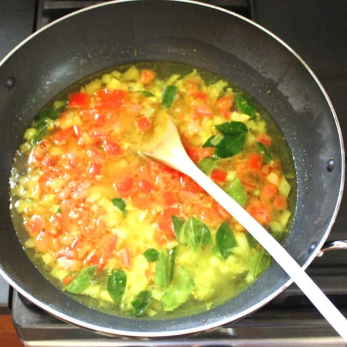 Rava upma spices, herbs and veggies and water boiling in a wok with a wooden ladle