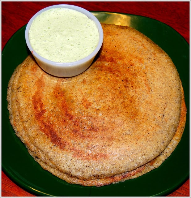 A stack of brown rice dosa in a green plate with coconut chutney