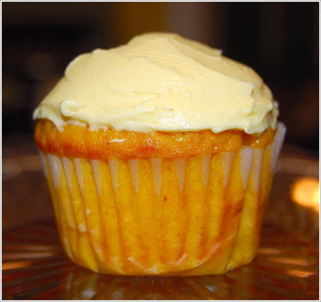 Front shot of a vegan mango cupcake with mango buttercream