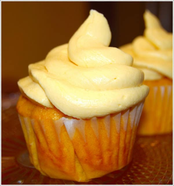 Two vegan mango cupcakes that are eggfree and dairyfree, piled with soft vegan mango buttercream frosting.