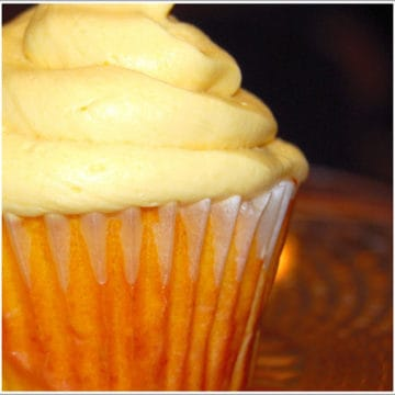 Closeup of a vegan mango cupcake piled high with mango buttercream frosting