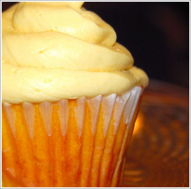 Closeup of a luscious, bright orange vegan mango cupcake with a soft, fluffy mango buttercream piled on top.