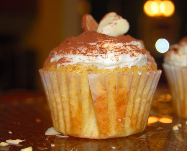 A lone, luscious orange cupcake with orange buttercream frosting decorated with almonds with a shower of cocoa on top.