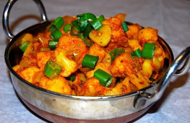 Closeup of cauliflower sabzi with tomatoes and scallions in kadhai.