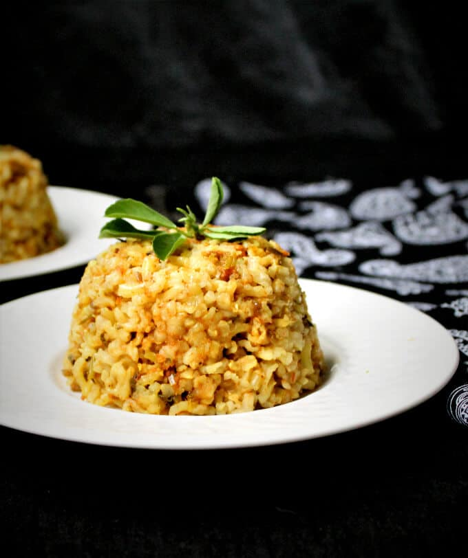 Methi Wara Chawar or Rice Pilaf with Fenugreek Leaves on a white plate with another plate and a black and white paisley napkin in background | HolyCowVegan.net