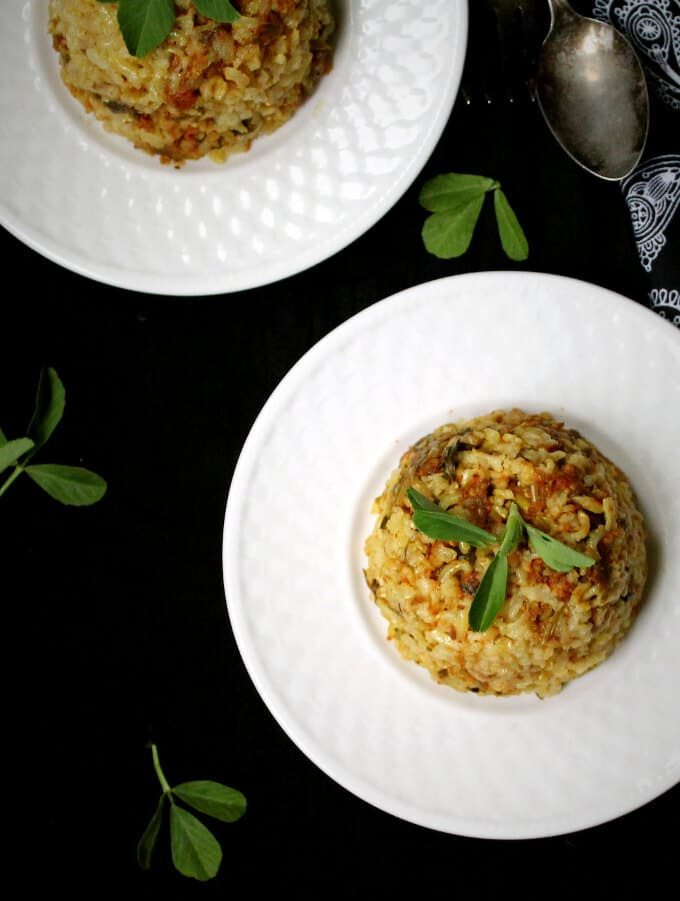 Overhead shot of Rice Pilaf with Fenugreek Leaves on a white plate, with another plate in the background | HolyCowVegan.net