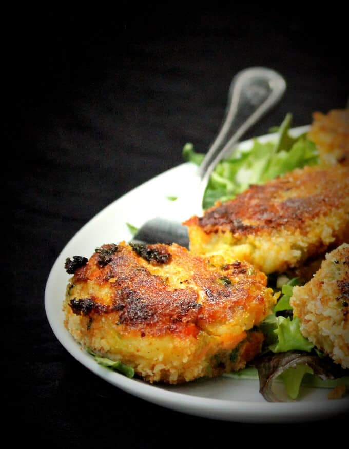 Crispy, crunchy, golden-brown veg cutlets on a white plate with greens.