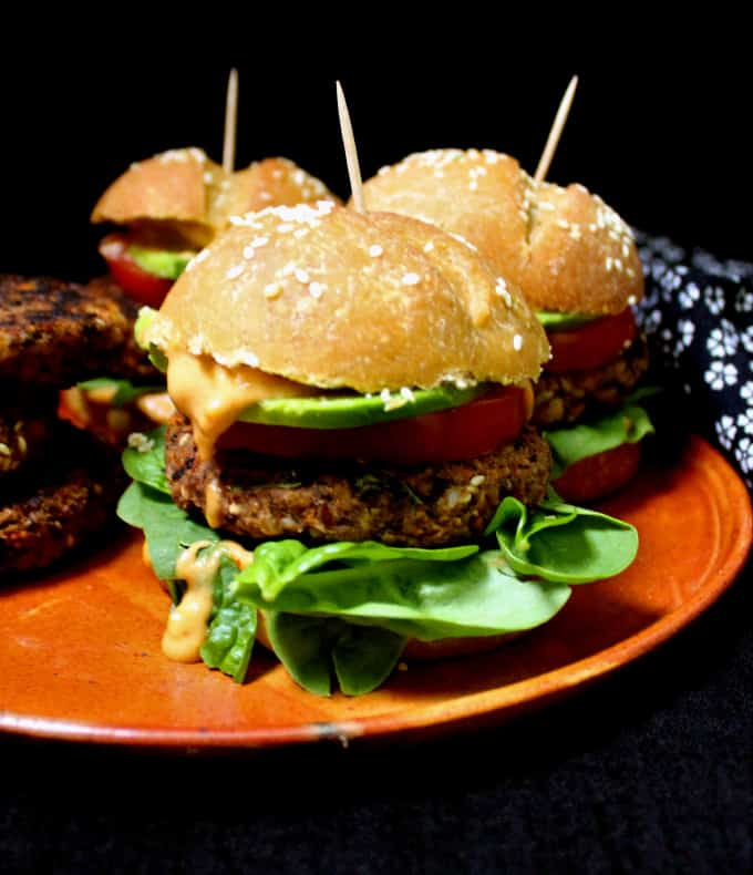 Front photo of vegan black bean burgers in homemade burger buns with greens, avocado and tomatoes.