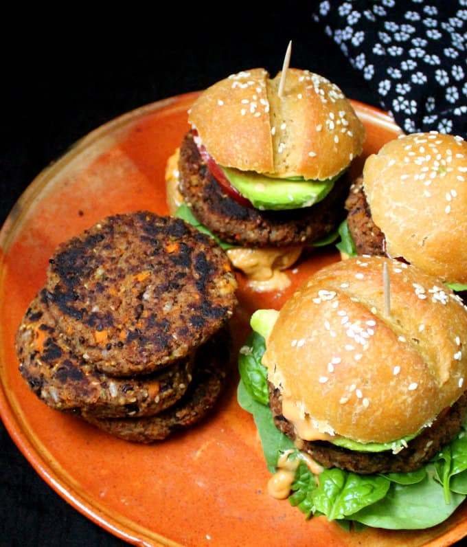 Front photo of Spicy Black Bean Burgers in burger buns with spinach and greens, avocado and tomato.