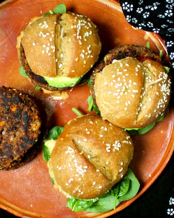 Overhead photo of vegan black bean burgers on an earthen tray.
